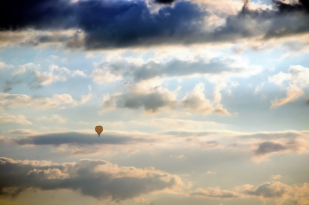 Yellow hot air balloon in flight against dramatic cloudy sky before sunset