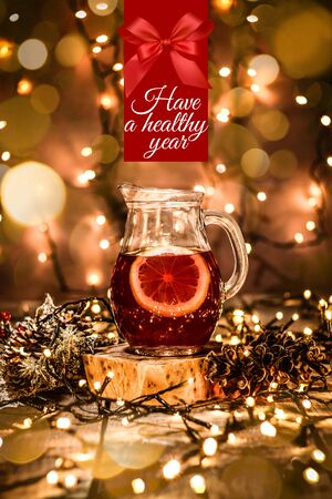 Closeup of a glass carafe with fruit tea and a piece of lemon in it on a wooden table with bokeh and christmas lights with text Have a Healthy Year Stock Photo