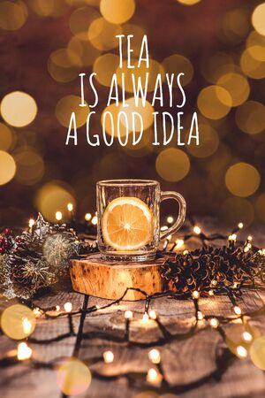 Holiday scene of a glass mug with fruit tea and a piece of lemon in it on a wooden table with bokeh and christmas lights with text Tea Is Always A Good Idea
