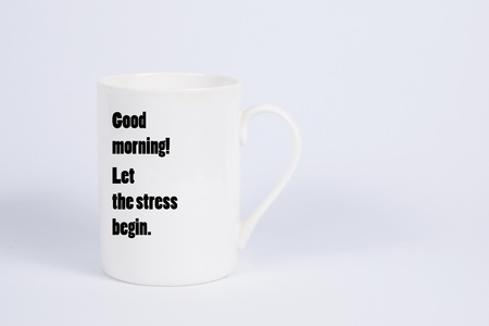 Close up of a simple white mug with the Good morning, let the stress begin quote Stock fotó