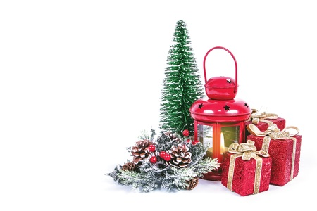 Close up of a christmas decorations with candle light, shiny presents, red lantern and ornaments on a white background with the message Merry Christmas Stock Photo
