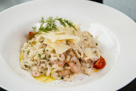 Close up of a risotto with vegetables and shrimps