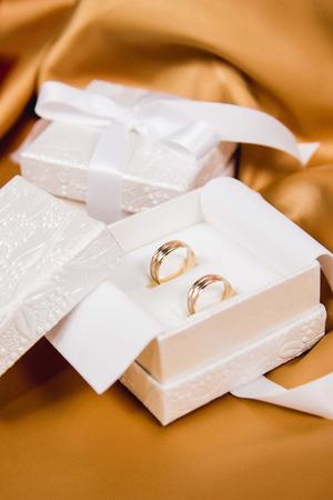 白い高級ボックスと黄色のシルクの背景にもう一つのボックスで結婚指輪の美しいクローズアップ