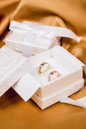 Beautiful close up of wedding rings in white luxury box and one more box on yellow silk background