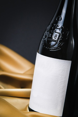 Close up of a white wine black ornament bottle with black background and yellow silk Editorial