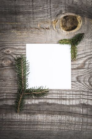 Empty piece of paper surrounded by pine tree branches on a wooden table 免版税图像