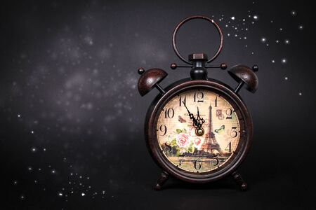 An old vintage clock with sparkles and stars on a black background Stock fotó
