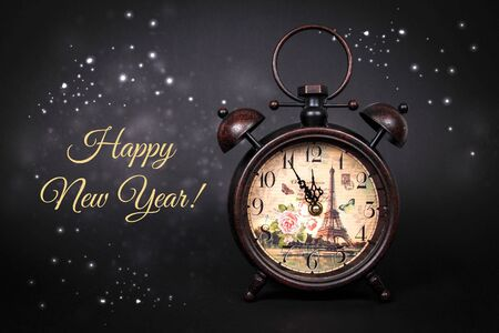 An old vintage clock with sparkles and stars on a black background with text Happy New Year Stock fotó