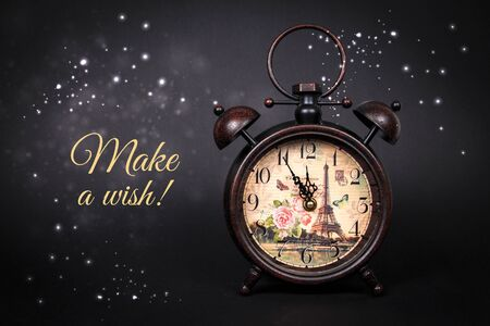 An old vintage clock with sparkles and stars on a black background with text Make a wish