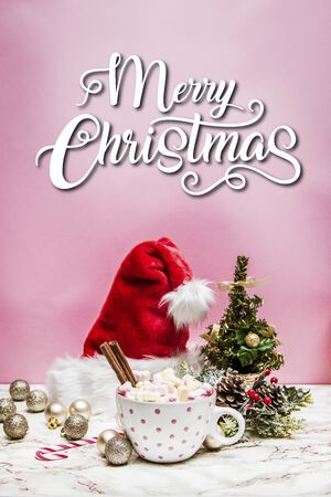 Pink white mug with marshmallows, Christmas tree, ornaments and Santa Claus hat on a marble and pink background with the quote