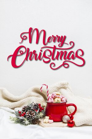 Red mug with marshmallows and winter ornaments on a white sheets with text Merry Christmas T