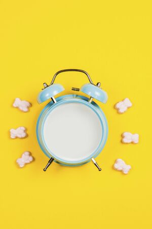 Vintage blue blank alarm clock on a yellow background with marskmallows as a decoration 写真素材