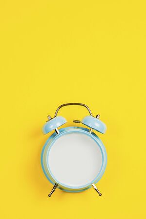 Vintage blue blank alarm clock on a yellow background 写真素材