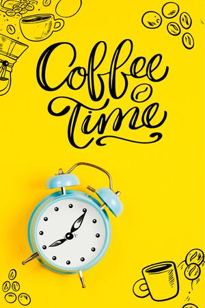 Blue alarm clock with graphics and text Coffee time on a yellow background