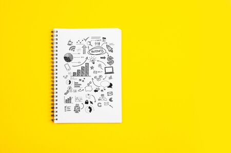 White paper page with doodles and business strategies on a yellow background Stock Photo