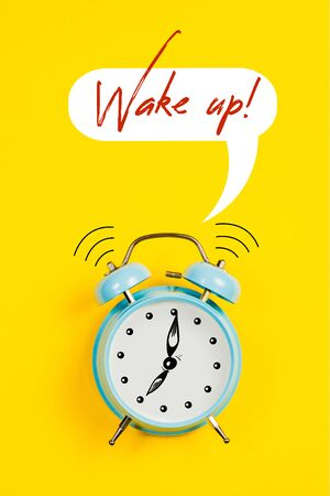 Blue alarm clock with graphics and text Wake up on a yellow background