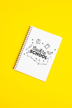 White paper page with doodles and text Back to school on a yellow background