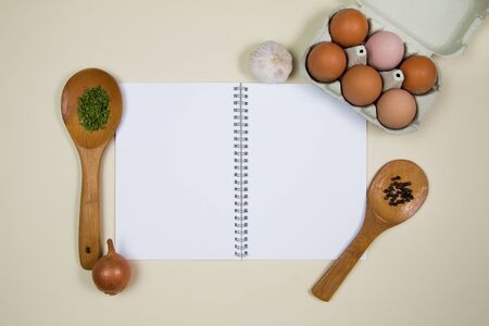 Wooden ladles with spices, eggs and garlic with a blank notebook page
