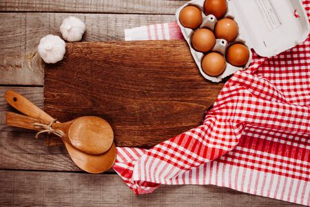 Wooden cutting board on a wooden background with garlic, ladles and eggs