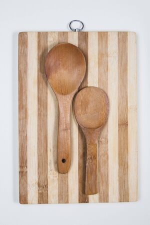 Wooden cutting board with wooden spoons on a table Stock Photo