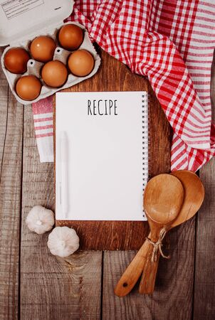 Wooden cutting board on a wooden background with garlic, ladles, eggs and a blank notebook with quote Recipe