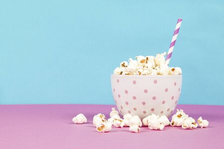 Fresh popcorn in a white pink bowl on pink and blue background