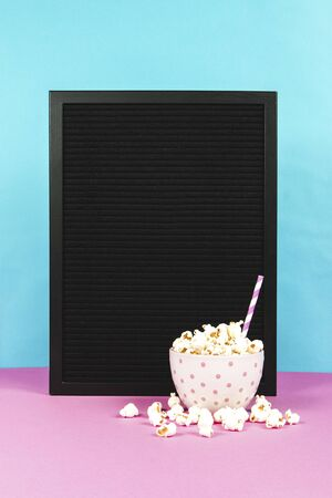 Fresh popcorn in a white pink bowl on pink background with the board