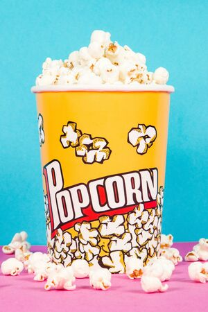 Yellow box of fresh popcorns on a pink and blue background