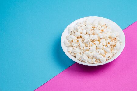 White bowl of popcorn on a blue and purple background