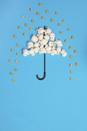 Umbrella and pouring rain drops made out of popcorn on a blue background