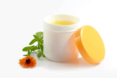 marigold: Cream pot with marigold on white background Stock Photo
