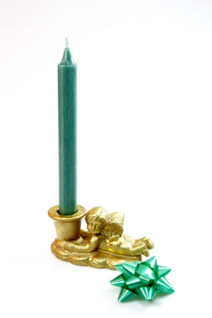 candleholder: Green candle in angel candleholder with green ribbon on light background