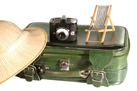 pith: Old suitcase with safari hat and little deck chair on light background