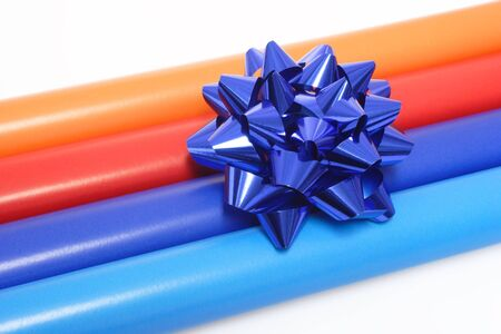 A view of colorful rolls of gift wrapping paper with a blue bow in the foreground.