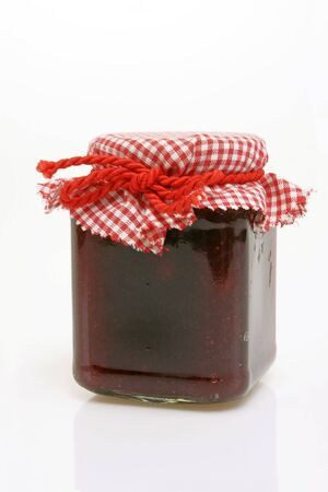 Jar of cranberry jam on bright background Stock Photo