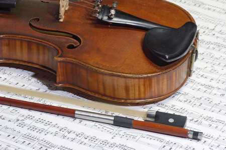 four chambers: Old violine in detail with a note sheet in background