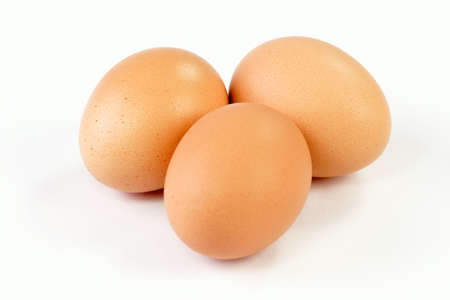sustenance: Close up of three brown eggs on bright background