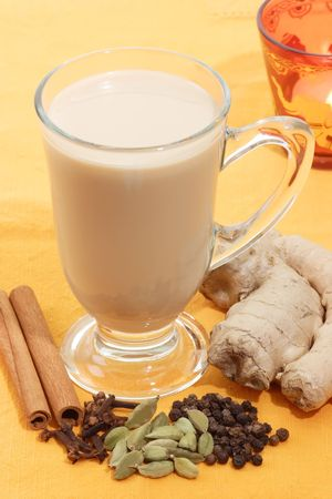 chai: Indian tea with different sorts of spices on yellow background