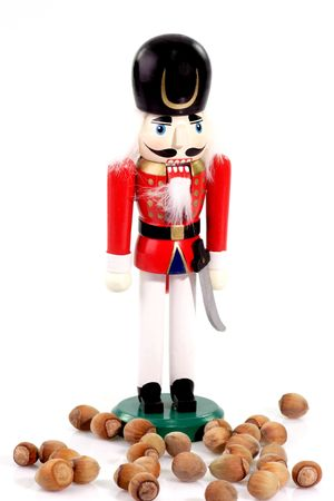 man nuts: Nutcracker man between nuts on bright background Stock Photo