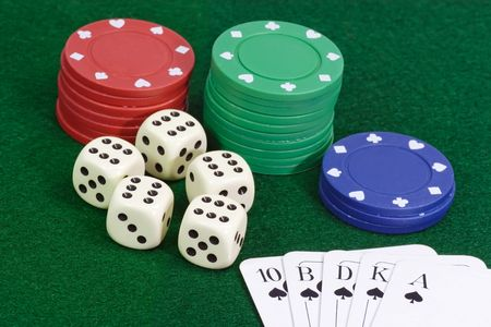 Poker chips with playing cards on green background photo
