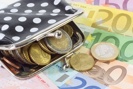 consuming: Money bag with euro banknotes and euro coins as background Stock Photo