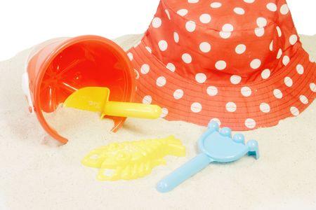 insolaci�n: Rojo sol y sombrero de juguetes en la arena