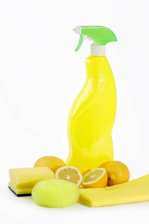 A yellow bottle of household cleaner spray with fresh lemons on bright background