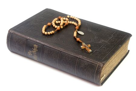 Ancient bible with rosary - isolated on white background