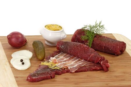 raw beef: Raw beef roulades with ingredients on a kitchen board