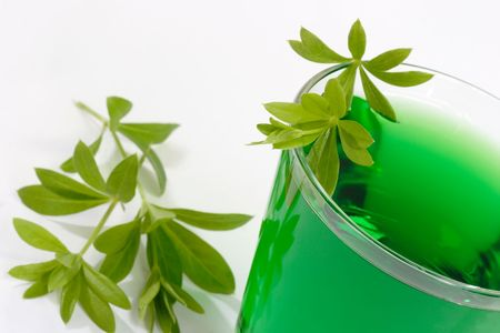 breen: Close up of green woodruff juice with leaves on bright background Stock Photo