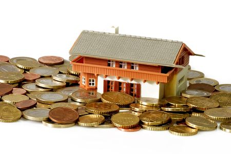economise: Toy house with euro coins on bright background
