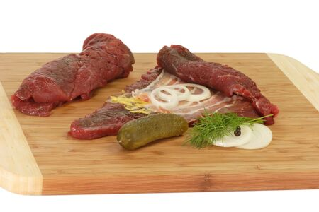 fare: Raw beef roulades with ingredients on a kitchen board