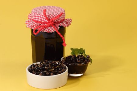 black currants: Glass of jam and black currants on yellow background