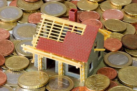bilding: Toy house with euro coins as background